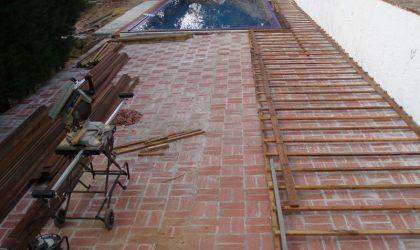Colocación de suelo de madera natural en la terraza con piscina